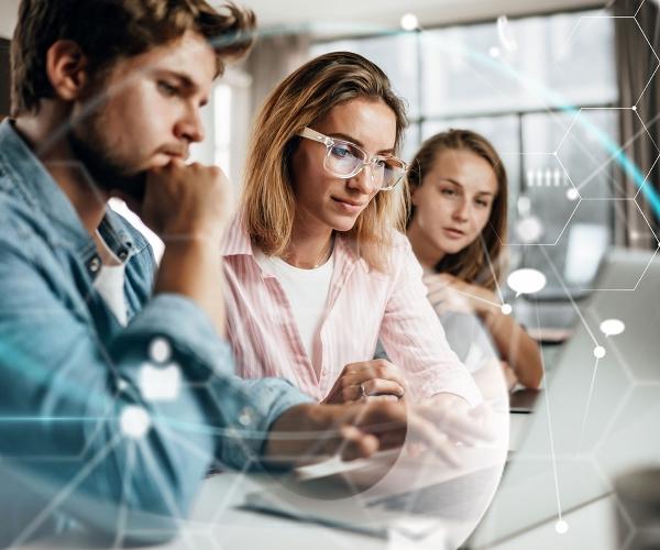 Junger Mann und junge Frau sitzen vor Computer